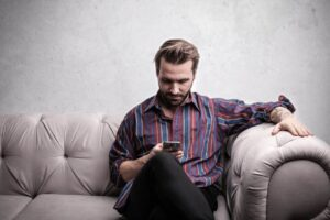 man sat on sofa reading phone