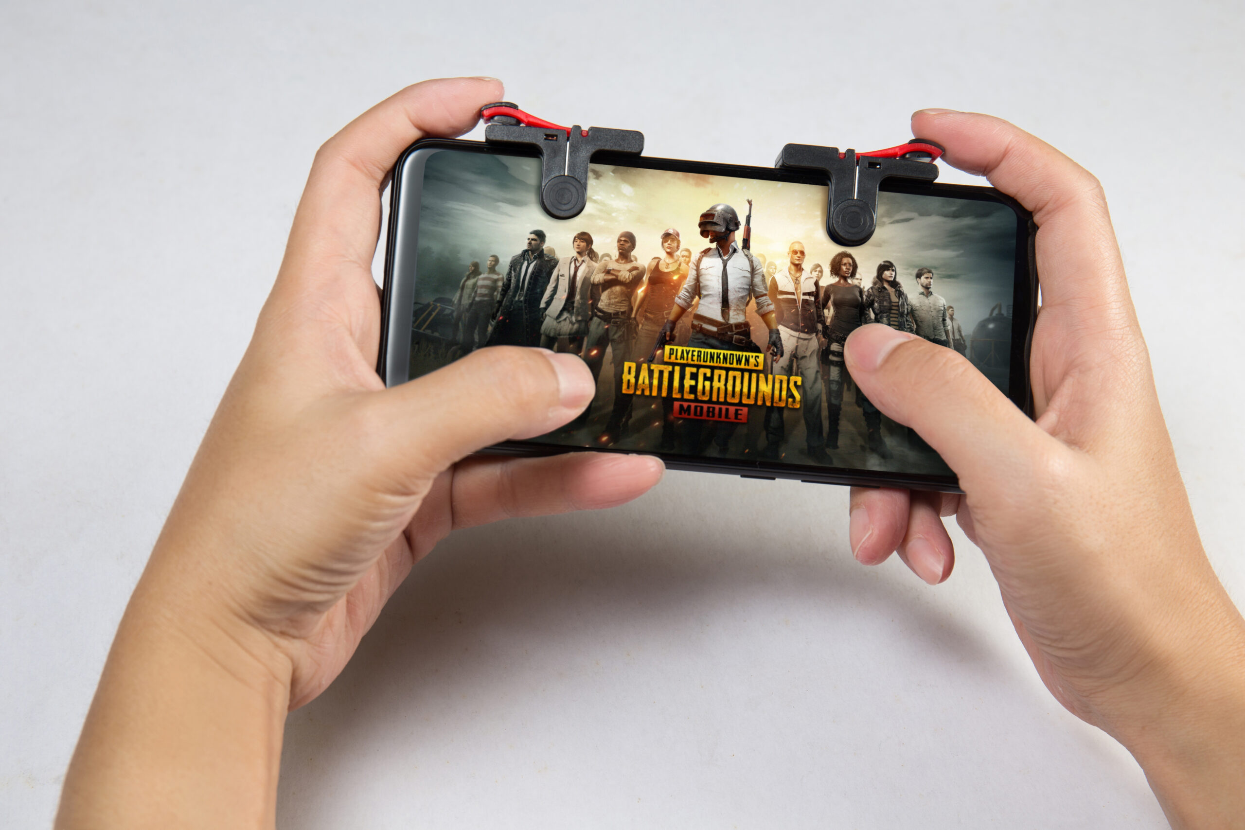Hand holding a smartphone with Player's Unknown Battleground also known as PUBG online shooting gaming