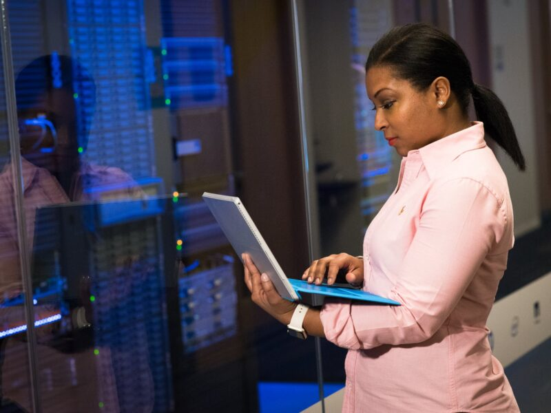 photo of woman holding a gray laptop in front of systems