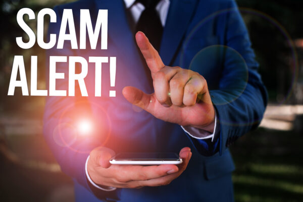 Text sign showing Scam Alert. Conceptual photo fraudulently obtain money from victim by persuading him Man with opened hands stands in suite. Concept with copy space and man. 1