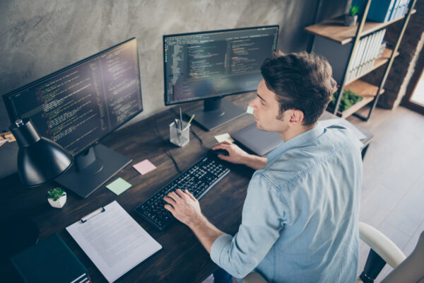 Top above high angle view portrait of his, he nice attractive focused skilled geek guy typing bug track report cyberspace security at modern industrial interior style concrete wall work place station