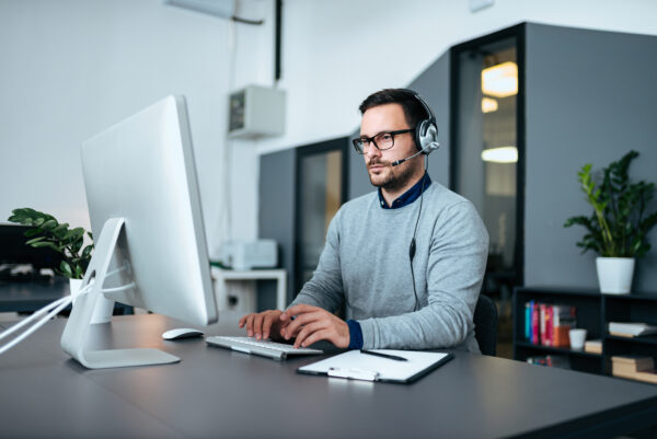 Young male customer support with headset working on the computer. 1