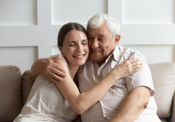 young woman hugging old man